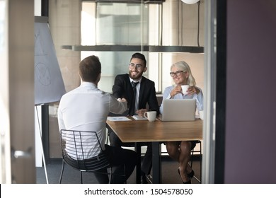 Rear view job vacancy applicant handshake greet arabian HR manager diverse people start job interview seated at desk in office, client and company executive managers finish negotiations feel satisfied