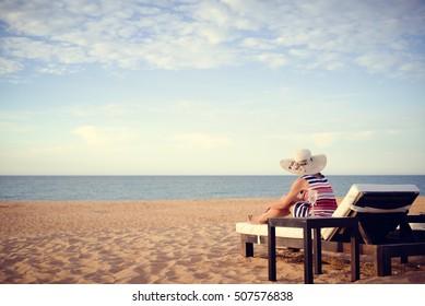 Rear view of joyful happy beautiful female on a tropical beach blue sky outdoors background