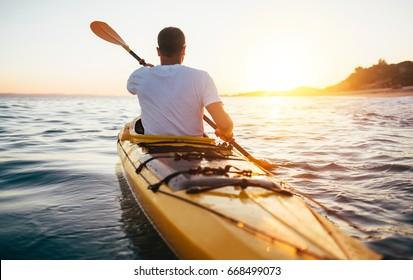 Rear view of kayaker man paddle kayak at sunset sea. Kayaking, canoeing, paddling
