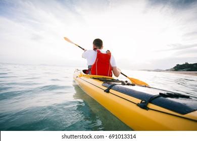Rear view of kayaker paddling. Paddling the sea kayak. Kayaking, paddling, canoe