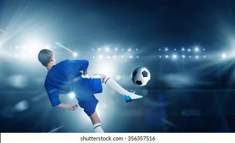 Rear view of kid boy in blue uniform on soccer stadium kicking ball