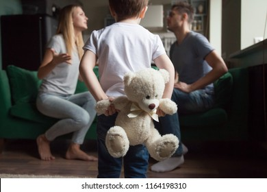 Rear view at kid boy holding toy while parents fighting, little son suffering from parents arguments, lack of attention or divorce, bad family relationships and psychological impact on child concept