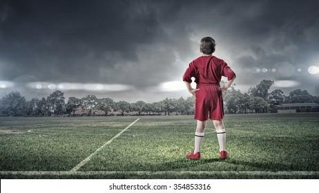 Rear view of kid boy in red uniform on soccer field