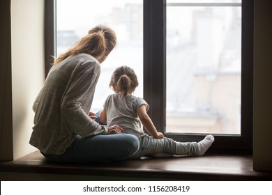 Rear view at kid daughter and single mother sitting on sill dreaming of good future concept, babysitter, nanny or young mom and child girl looking outside window thinking of new goals feeling hopeful