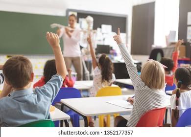 Hintere Ansicht von Kindern, die Händezuheben, während Lehrer die Funktionsweise des menschlichen Skeletts in der Schule erklären