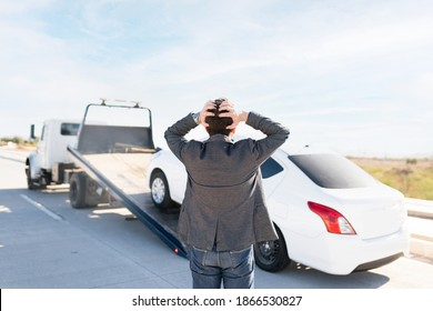 Rear view of a latin man in his 30s looking angry because he is watching his car being towed on a tow truck from the side of the highway