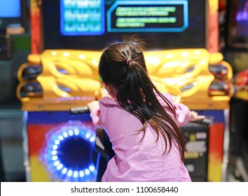 Rear view of little Asian kid girl playing arcade video game. Motorcycle Racing.