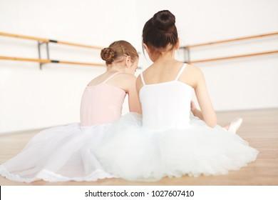 Rear view of little ballerinas having rest on the floor between classes of dancing