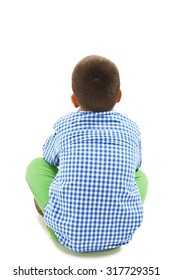 Rear view of little boy sitting on floor. Isolated on white background