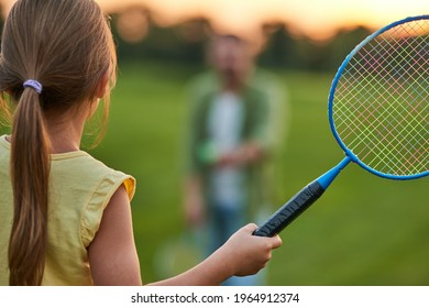 Rear view of little girl holding badminton racket while playing with her father outdoors in the park on a summer day