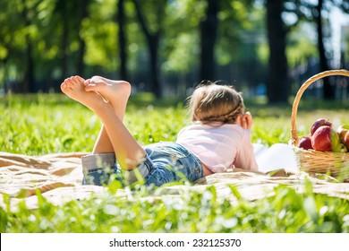 Rear view of little girl lying in summer park