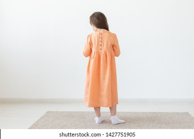 Rear view of a little girl posing in a long peach dress with buttons on the back and a white background. The concept of unique children's dresses. Advertising space.