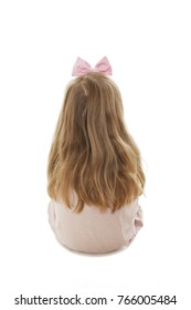 Rear view of little girl sitting on floor, looking at wall. Isolated on white background