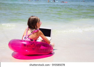Rear view of little girl wearing pink swimsuit sitting on swim ring on beach, using laptop and looking at sea waves during summer vacation