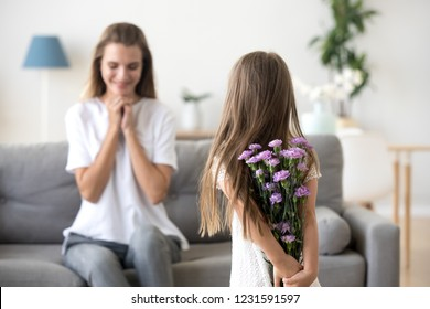 Rear view at little kid daughter holding violet flowers congratulating happy young mom with mothers day or birthday, child girl hiding bouquet behind back making surprise to grateful mommy at home