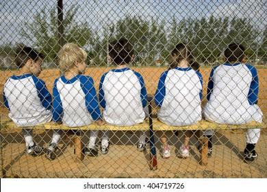Rear view little league baseball team sitting on bench