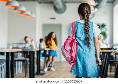 rear view of little schoolgirl in dress walking at school cafeteria