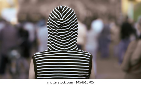 Rear view lonely girl in a vest with a hood stands against the crowd. Background in blur.