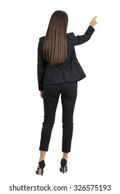 Rear view of long dark hair beauty pointing or presenting on her right side. Full body length portrait isolated over white studio background.