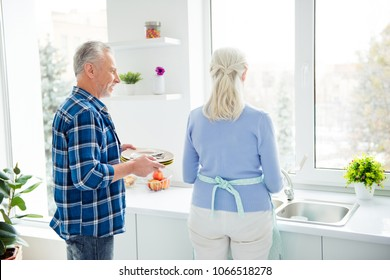 Rear view of lovely attractive stylish couple cleaning up table after breakfast in the morning together, woman washing dishes, man bringing dirty plates, standing near sink in flat, apartment