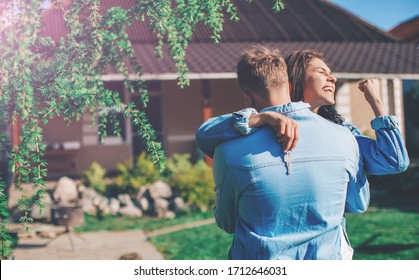 Rear View Of Loving Couple Walking Towards House. Young smiling couple showing keys to new home hugging. Couple in love. Background. Love concept. Happiness. Lifestyle. Emotion. Concept. Lovely.