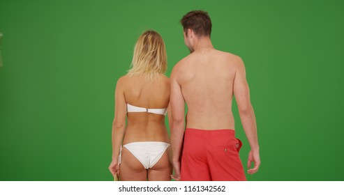 7e5435e4aed36 Rear view loving white couple in swimsuits holding hands on green screen