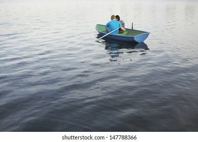 Rear view of a loving young couple cuddling in rowboat at lake