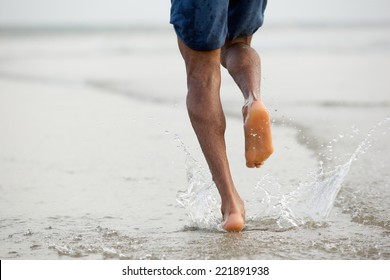 Rear view low angle view of a man running barefoot in water