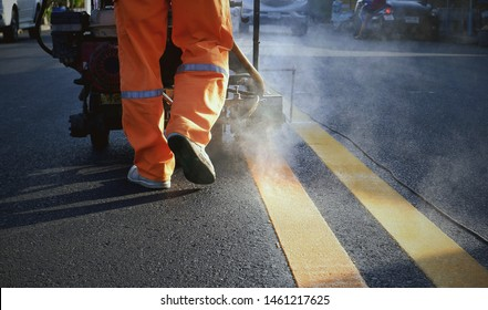 Rear view and low section of road worker with thermoplastic spray road marking machine working to paint double yellow lines with steam on asphalt road surface in evening time, construction concept