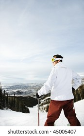 Rear view of a male adult skier on a Colorado ski slope with mountains in background. Vertical shot.