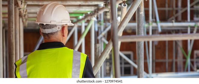 Rear view of male builder construction worker on building site wearing hard hat and hi vis vest panoramic web banner
