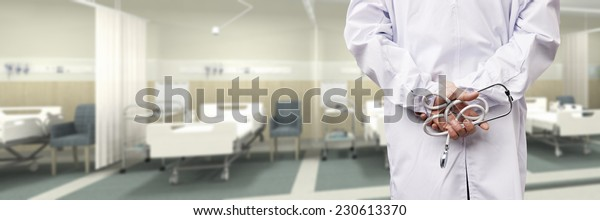 rear view of a male doctor with stethoscope in hospital ward.