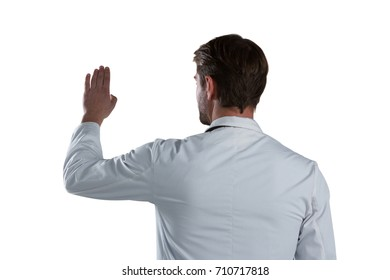 Rear view of male doctor using invisible screen against white background