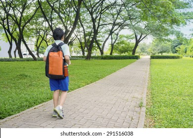 Rear view of male elementary school student walking alone to school while carrying backpack