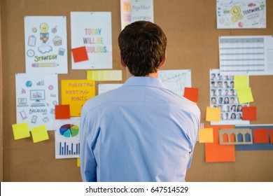 Rear view of male executive looking at the bulletin board in office