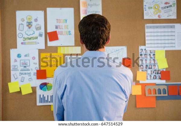 Vista posteriore del dirigente maschile guardando la bacheca in ufficio