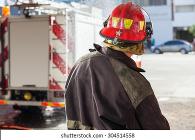 Rear view of male firefighter spraying water at fire station