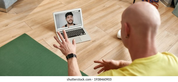Rear view of a male fitness instructor explaining workout technics online, having video conference, mature man conducting virtual fitness class by webcam on laptop. Sport, healthy and active lifestyle