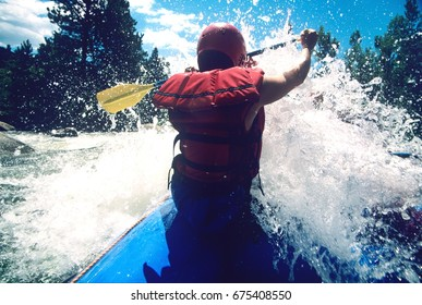 Rear view of a male kayaker paddling through rapids