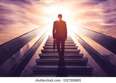 Rear view of male manager carrying a suitcase while walking upward on the stairs with modern city background