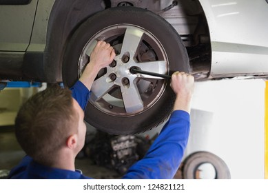 Rear view of male mechanic fixing car tire