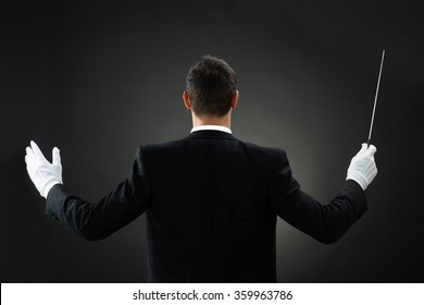 Rear view of male music conductor holding baton against gray background