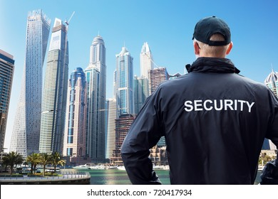 Rear View Of Male Security Guard Looking At City Skyline