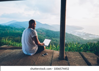 Rear view of male traveler blogger work remote on netbook computer while enjoying amazon nature landscape view outdoors. Young man using online banking for sending money everywhere you are from laptop