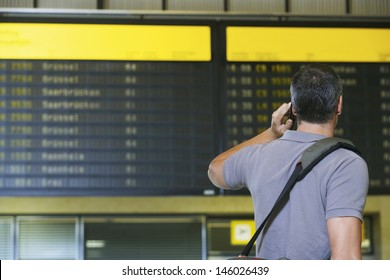 Rear view of a male traveler using mobile phone in front of flight status board in airport