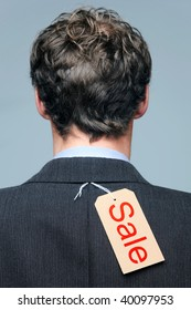 Rear view of a male wearing a suit jacket with a Sale label on it.