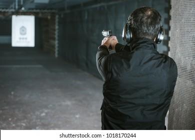 rear view of man aiming gun at target in shooting range