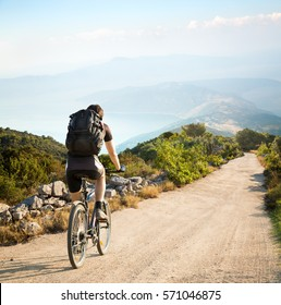 Rear View of a Man with Backpack Riding a Bicycle in the Mountains by the Sea. Beautiful Nature Background. Healthy Lifestyle and Bike Travel Concept. Toned Photo with Copy Space.