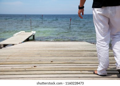 Rear view of a man in a black shirt and white trousers walking along a wooden pier on the Mediterranean coast