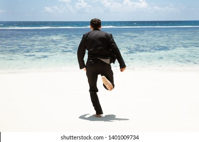 Rear View Of A Man In Black Suit Running Barefoot Toward The Sea At Beach
